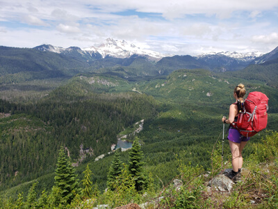 Kristine of Hikes Near Vancouver wearing a 60L Vaude backpack on the edge of a cliff overlooking an amazing valley in British-Columbia