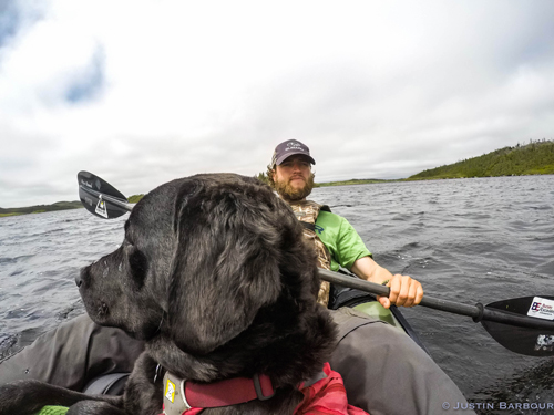 Justin Barbour exploring in his canoe with Saku looking over the horizon