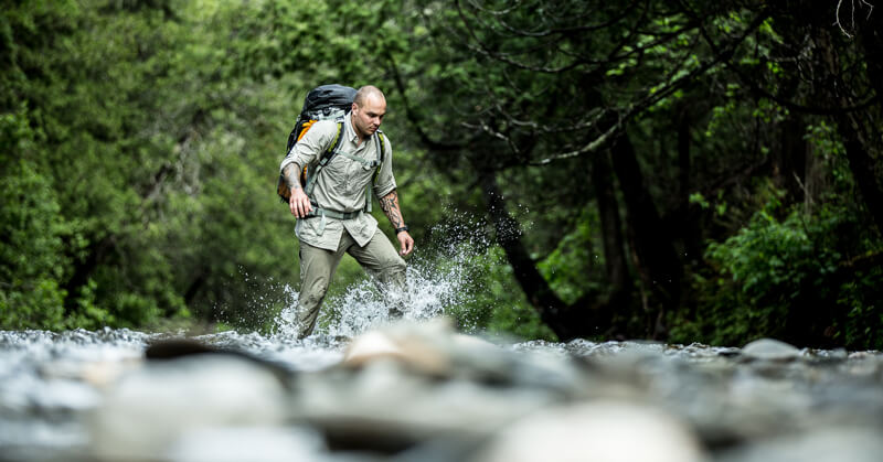 Keven Martel crossing a river while on a expedition